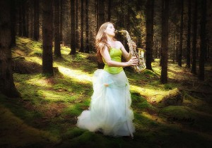 Charlotte spelar saxofon i skogen.
